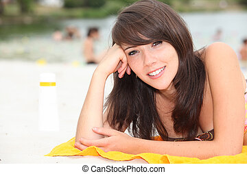 Teenage girl sunbathing on a beach