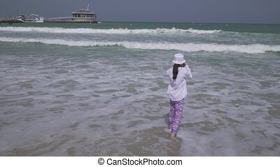 Teenage girl takes pictures of the sea waves of the Persian...