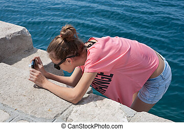 Teenage girl taking photos by the sea