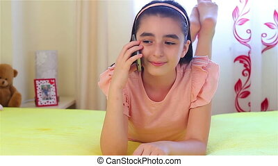 Teenage girl talking on smartphone lying on bed