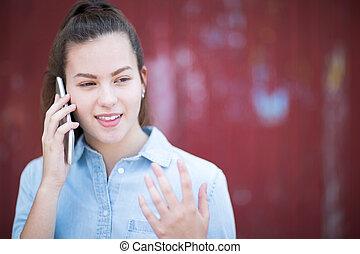Teenage Girl Talking Outside On Mobile Phone In Urban Setting