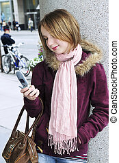 Teenage girl text messaging on cell phone