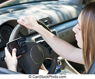 Teenage girl texting and driving - Teenage girl texting on...
