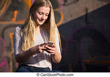 Teenage Girl Texting On Mobile Phone In Playground