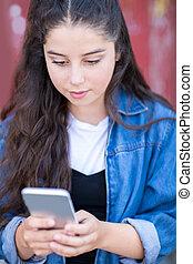 Teenage Girl Texting On Mobile Phone In Urban Setting