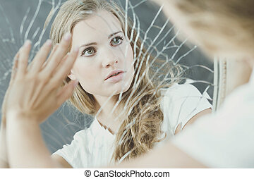 Teenage girl touching broken mirror - Teenage girl with...