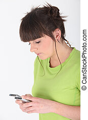 Teenage girl using cellphone on white background