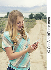 Teenage girl using cellphone walking down a country dirt road