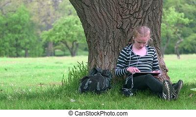 Teenage girl using digital tablet computer in summer park