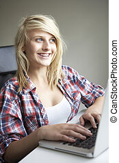 Teenage Girl Using Laptop At Home