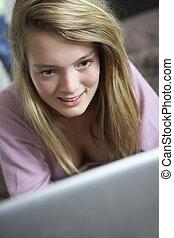 Teenage Girl Using Laptop At Home