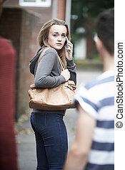 Teenage Girl Using Phone As She Feels Intimidated On Walk...