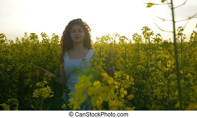 Teenage girl walking and smiling in canola flowers field at summer sunset