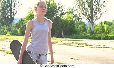 Teenage girl walking with skateboard in summer day - Teenage...
