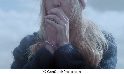 Teenage girl warming hands with breathing