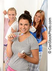 Teenage girl washing her teeth with friends
