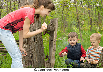 Teenage girl watching two young boys at play