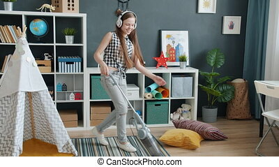 Teenage girl wearing headphones dancing and cleaning carpet with vacuum cleaner at home