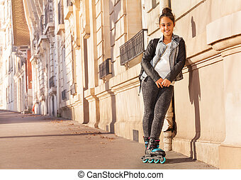 Teenage girl wearing roller skates riding in town