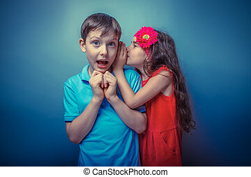 Teenage girl whispering in the ear of a secret teen boys on a g