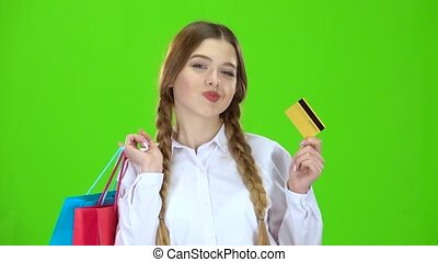 Teenage girl with a credit card and packages in her hands . Green screen