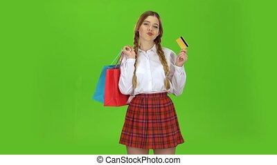 Teenage girl with a credit card and packages in her hands. Green screen