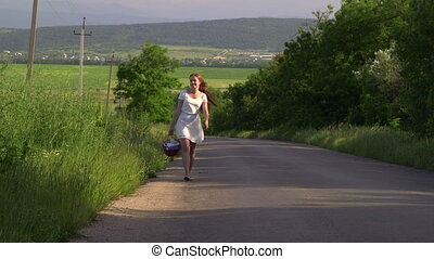 Teenage girl with basket walking along a country road