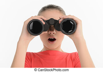 Teenage girl with binoculars. Excited teenage looking through binoculars while isolated on white