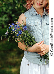Teenage girl with curly hair is holding blue bouquet of meadow flowers