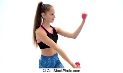 Teenage girl with dumbbells in hands - A teenage girl with...