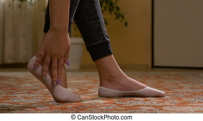 Teenage girl with flats rubbing her tired sole foot muscles relaxing her leg