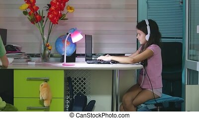 teenage girl with headphones indoors sitting with a laptop....