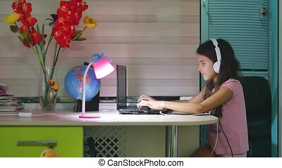 teenage girl with headphones sitting with a laptop....