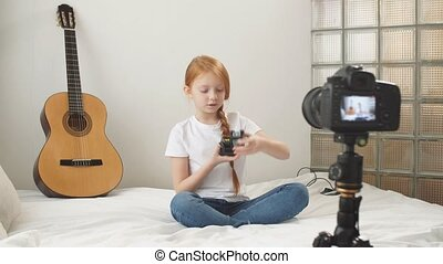 teenage girl with long red hair Caucasian blogger shows and talks to the camera about new technologies, toys and modern devices