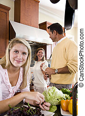 Teenage girl with parents in kitchen smiling