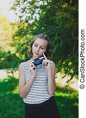 Teenage girl with retro camera in the park
