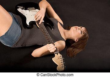 Teenage girl with rock guitar lying down on floor