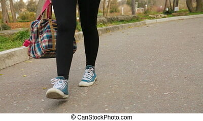 Teenage Girl With Roller-Skaters Is Walking In The Park
