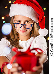 Teenage girl with Santa hat holding a present