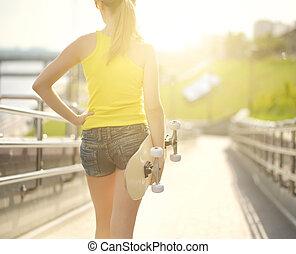 Teenage girl with skateboard