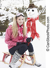Teenage Girl With Sledge Next To Snowman