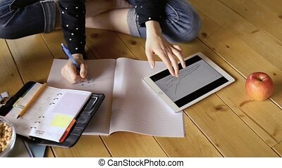 Teenage girl with tablet sitting on the floor, studying