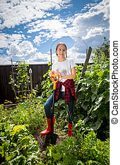 Teenage girl working at garden at bright sunny day