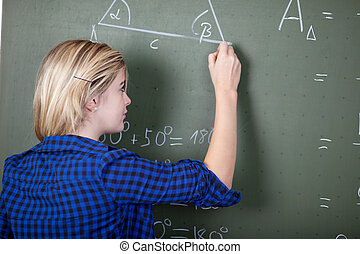 Teenage Girl Writing On Chalkboard - Rear view of teenage...