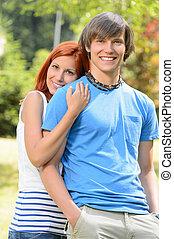 Teenage girlfriend embracing her boyfriend in park