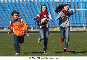 Teenage girls and boy enjoy to running on the stadium field....