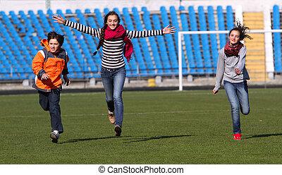 Teenage girls and boy enjoy to running on the stadium field.