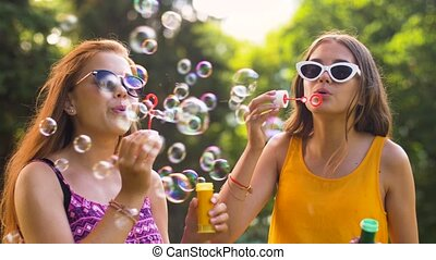 teenage girls blowing bubbles in summer park - leisure and...