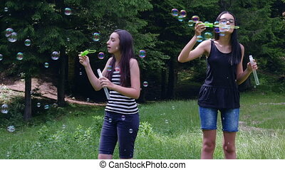 Teenage girls blowing soap bubbles in summer time - Teenage...