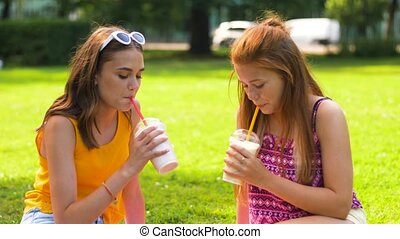 teenage girls drink milk shakes at picnic in park - leisure...